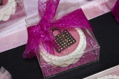 Glam party favor.  Chocolate covered Oreo decorated with pink luster icing sheet which has been embossed using e-bosser.  Purse made in deco gel  and trimmed with fondant ruffle.