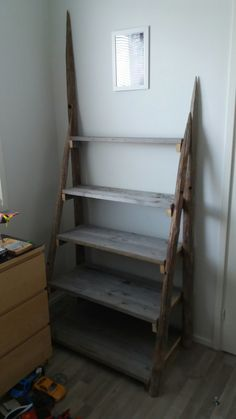 I made this rustic looking shelf from hay poles and salvaged pallet wood for my son's legos. Reclaimed Wood Projects, Reclaimed Lumber, Pallet Wood, Wood Pallets, Diy Shelving, Ladder Bookcase, Legos, Shelf, Woodworking