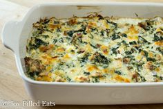 cooked chicken and spinach in a creamy sauce in a large white casserole dish