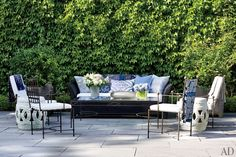 The pool terrace is outfitted with a cocktail table by Janus et Cie; the chair cushions are covered in a Ralph Lauren Home canvas, and the ceramic taborets are from Bungalow.