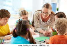 Portrait of diligent schoolkids and their teacher talking at lesson