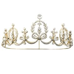 A Late Victorian diamond tiara,  with a top central old brilliant-cut diamond surmounting a diamond set laurel foliate and ribbon motif, with swag and ribbons in between, all silver on gold, to a gold frame convertible into a necklace,~ 11 carats, circa 1890.