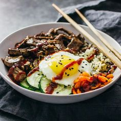 You'll love this easy recipe for homemade bibimbap! This tasty Korean beef bowl has marinated beef, mushrooms, zucchini, rice, and a delicious spicy sauce.