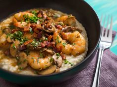Shrimp and Gruyère Cheese Grits With Bacon and Mushrooms Recipe | Shrimp and grits is a dish with so many renditions, the only thing you can really count on is that it contains shrimp...and grits. Often there's pork, sometimes mushrooms, and the amount of gravy can range from none to tons. This recipe features plump shrimp, seared mushrooms, crispy bacon, and rich cheese grits infused with layers and layers of flavor.