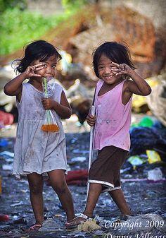 Little girls posing in Smokey Mountain, Philippines. Photographer: Dennis Villegas