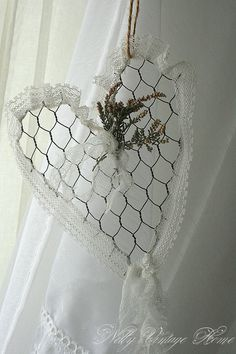 Chicken wire heart, trimmed out in lace with sprigs of dried flowers - this one is just snipped out, but I would cut wire and form the outline of the heart, then twist the ends of the chicken wire around it to stabilize, and cut down on sharp points. Can do other shapes as well, but hearts are great. from nelly vintage home - #chickenwire #wire #heart #lace #crafts tå√