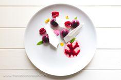 Dolce al piatto con semisfere di semifreddo di frutti di bosco, scaglie di meringa, salsa ai lamponi, lamponi freschi e fiori eduli