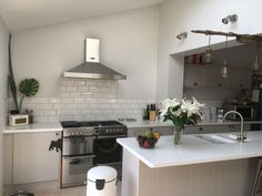Howdens Burford stone kitchen with a white Corian worktop, white sunbway tiles and grey grout