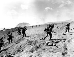 CAMINO AL SURIBASCHI,  Marines de la cuarta división se adentran en la playa en Iwo Jima. Un marine muerto yace a la derecha en primer plano. El monte Suribachi, al fondo, se convirtió en una colmena armada de tropas japonesas.