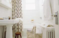 White vintage bathroom with Albert Hadley shower curtain (via Domino)