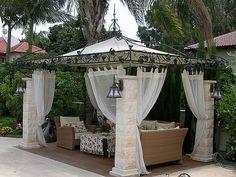 pergola en fer forgé, rideaux blancs et mobilier de jardin
