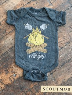 """Dress up your outdoorsy babe in this adorably printed jumper, decorated with two familiar sights: roasting marshamallows and campfire. The center reads, """"Happy Camper,"""" in vintage-inspired letters, and the hand-illustrated design is printed on super soft triblend fabric."""