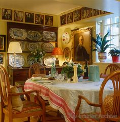 A dresser displaying blue and white platters stands at one end of the breakfast room and the walls are filled with portraits and framed photographs ~ Mark Birley