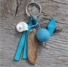 Kuta  Porte clés avec perles en feutrine, céramique, métal et rocailles. Bois flotté. Coquillage. Galon turquoise. Cordon coton ciré.  Longueur : 13 cm  Prix : 12 euros