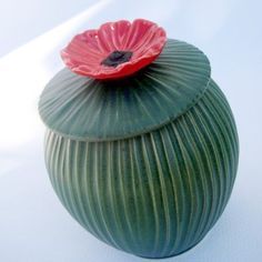 Green jar with red poppy by Alina Hayes