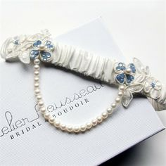 Fashioned from superior quality ivory silk dupion, the Sweetheart couture bridal garter is adorned with hand-beaded appliqués featuring lustrous freshwater pearls and opal blue Swarovski crystals for your traditional 'Something Blue'. A single strand of ivory Japanese freshwater pearls drape underneath for a vintage touch.