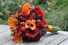 Vibrant fall wedding bouquet made of orange calla lily, red roses, ranunculus, berries.