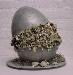 een keramiek ei in twee delen, gedrybrushed met zilver en opgevuld met korstmos en eitjes