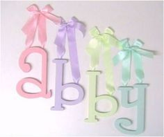 ribbon-hung wooden baby name wall letters, I like this for a boy too, but instead of ribbon, it could be rope or something.