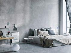 Bed on floor in concrete / gray bedroom
