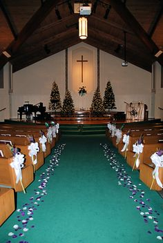 "Church Decorations for a ""winter"" wedding featuring purple and teal. Christmas trees with plain white lights. Pew bows feature peacock feathers and purple flowers."