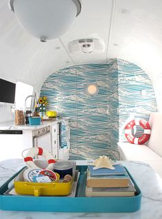 This nautical airstream is for the adventurous spirit. The red life preservers are just the right amount of color for the blue and white space.