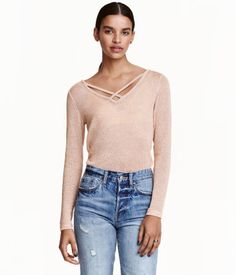 Beige/glittery. Loose-knit sweater with long sleeves. V-neck with crossover straps at neckline.