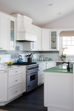 Kitchen boasts a high ceiling that touches the roof with lights that are put directly into the ceiling. Kitchen with aqua blue mosaic tiling and turquoise counter top. #Kitchen #Turquoise #Countertop #Knobs Out in Design.