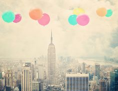 Imagine flying high over the Empire State Building with the whole of Manhattan spread out before you. This fantasy can play out in your mind every time you look up and see Maybe Sparrow's Balloons Over New York photo print hanging on your wall.