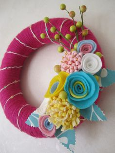 Pink Yarn Wreath with Teal Felt Flowers 10 via Etsy  So many color possibilities.