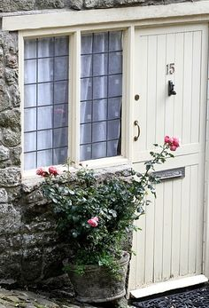 ideas for front door. notice the plank like design on the door. Love the planter with roses next to the front door too! White Cottage, Rose Cottage, Cottage Style, Cottage Door, Shabby Cottage, Half Doors, Windows And Doors, Little White House, Entrance Doors