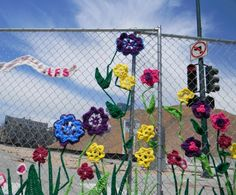 Fun flower yarnbomb on a fence. Ladies Fancywork Society