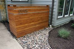 cedar screen (to hide trash can) with aluminum channel detail and house numbers lit from above