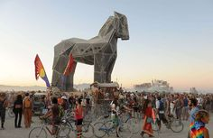 People gather around the Trojan Horse as it's pulled across the playa at the…