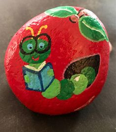 Adorable dark and light green inchworm reading a book in teachers bright red apple. This little guy is so cute on teachers desk, in the library, kids room, playroom or even on the windowsil in the kitchen. Makes a great addition to any classroom, and fun, unique gift! Painted rocks are fun, unique pieces of art that make wonderful display pieces, garden stones, paperweights, pet rocks, good luck charms and gifts! If youve never owned a painted rock, let me assure you they are charming…