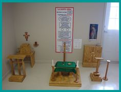 From Chiquitos Preschool comes this photograph of their model altar center.  On the left is the tabernacle and sanctuary lamp with a kneeler for adoration.  On the right is a sacristy cabinet and ambo.  In the center is the altar dressed with a child sized frontal, candles, etc.  The Synthesis of the Eucharist chart would not ordinarily be hung behind the altar (a 3-6 yr. old material), but it would be placed with the 6-9 year old materials related to the Rite of Eucharist.