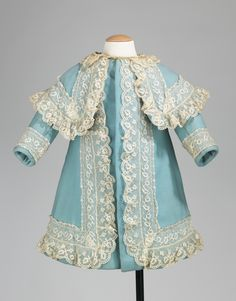 A girl's wool coat with lace trim from between 1885 and 1890.