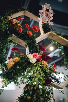 Add some geometric decor to your modern wedding reception, like these multicolored flowers hanging from wooden honeycomb structures above tables.