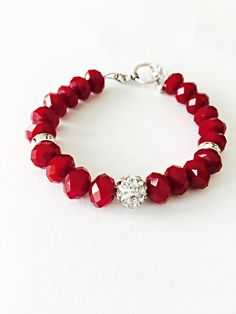 Beautiful red dark bracelet,bright red crystals and in the middle a epoxy bead. * Bright red 10mm crystal *12mm epoxy bead *silver rondelle Measure: 7 inch