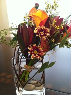 I made these fall centerpieces so that hand-tied flowers could be sent home with guests, but I still kept my containers with the willow and river rock. The hand-tied bouquets are made up of Sunset Proteas, Orange Callas, pompoms, yellow waxflowers, and seeded eucalyptus.