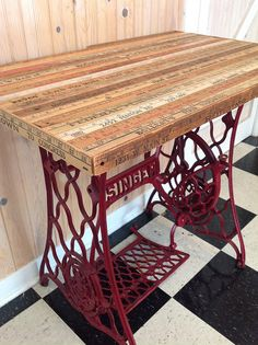 An antique Singer treadle sewing machine base finds new life as a table with the addition of vintage yardsticks nailed to an oak base- I love this