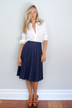 White shirt, navy pleated skirt and brown wedges.
