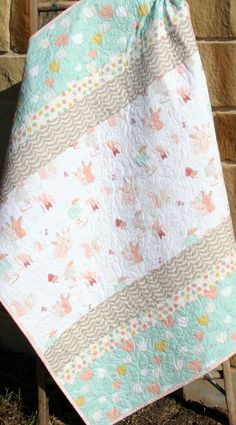 """Adorable modern stripe girl quilt in coral pink, mint green, and grey with bunnies, tulips, flowers, and other modern designs. You can choose the size baby (38""""x45"""") or toddler (38""""x54""""). So beautiful look closely at the quilting which really brings this quilt to life! QUILTERS: You can purchase the QUILT KIT here. A quilt is three layers stitched together, with the middle layer being a natural cotton batting. Professionally quilted on a long arm quilting machine; stitches are even, tight…"""