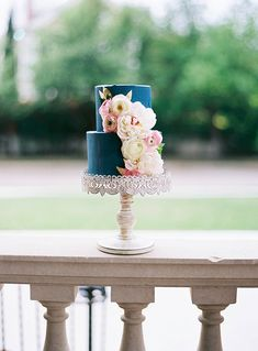 Two-tier navy cake with cascading flowers