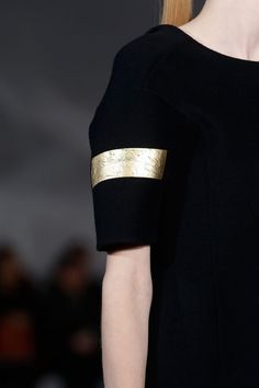 Black dress sleeve with a band of gold cracked leather; chic fashion details // Jil Sander