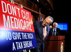 Trump reaches out to Democrats in bid for 'great' health law - Senate Minority Leader Chuck Schumer of New York, followed by Sen. Bernie Sanders, I-Vt., look at a poster at the start of a news conference on Capitol Hill in Washington, Wednesday, October 4, 2017, urging Republicans to abandon cuts to Medicare and Medicaid. (AP Photo/Manuel Balce Ceneta): Senate Minority Leader Chuck Schumer of New York looks at a poster at the start of a news conference on Capitol Hill on Oct. 4.
