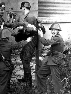 hier ziet u dat een man is opgepakt na een vluchtpoging door de Berlijnse muur