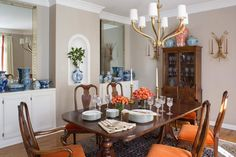 Orange-cushioned chairs are a bright pop of color in this formal, transitional dining room. The elegant, dining table setting boasts brass candle holders and crystal stemware, while a collection of blue and white vases makes for a stunning display.