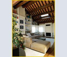 La zona conversazione, sotto il soffitto con le TRAVI ORIGINALI in legno, si sviluppa intorno al camino. Le SEDUT E Mex Cube sono un progetto di Piero Lissoni per Cassina e i tappeti sono di LE (Limit