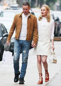 Kate Bosworth wears a white turtleneck, white overall dress, lace-up sandals, and a top-handle bag